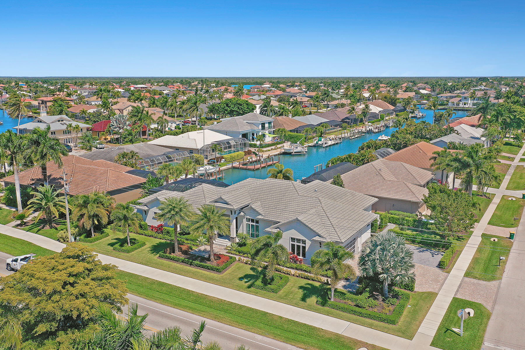 Gorgeous contemporary home located on an oversized corner lot with water direct access to the Marco River. This luxurious furnished home has it all with gorgeous decor and exquisite lavish details throughout. Light and bright open floor plan with spacious great room design and separate office that include beautiful built-ins. A Chef's dream gourmet kitchen that comes with custom cabinetry, over-the-top appliances, pantry, two breakfast bars, and separate dining area. Whole-house automation, Crestron lighting control system, tray ceilings, designer tile, baths, counter-tops, fixtures, and top-quality finishes. The sweeping veranda is outdoor living at it finest and has everything you need with pool, spa, bar, summer kitchen, drop down shutters /screens, and plenty of space to entertain and enjoy the long water canal views. Impact glass windows and doors, whole-house generator, pavered driveway and sidewalk that encircles the home for easy walking. Extended parking for additional vehicles and side entry garage. Deeded dock with lift that includes your own sundeck! New Seawall 2016. Surrounded by plush tropical landscaping. Make this home your piece of paradise today.