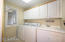 Laundry off the kitchen with sink, closet, storage & access to garage