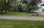 Paved driveway between front yard and shed with entrance from both sides of the property.