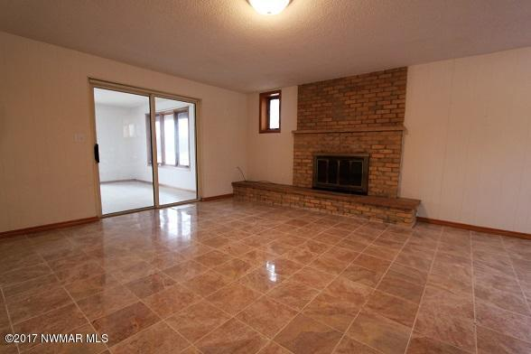 downstairs family room with marble floors and fireplace