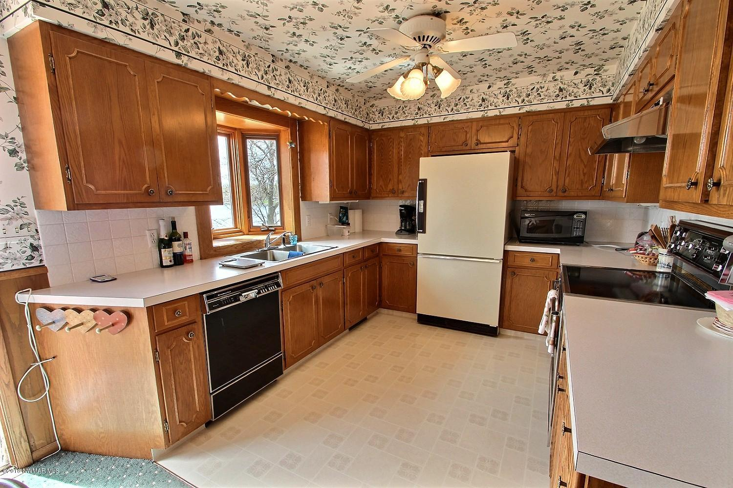 View of the kitchen including dishwasher, stove, fridge, tons of cabinet and counter space, bay window and ceiling fan. There is plenty of space here for entertaining!