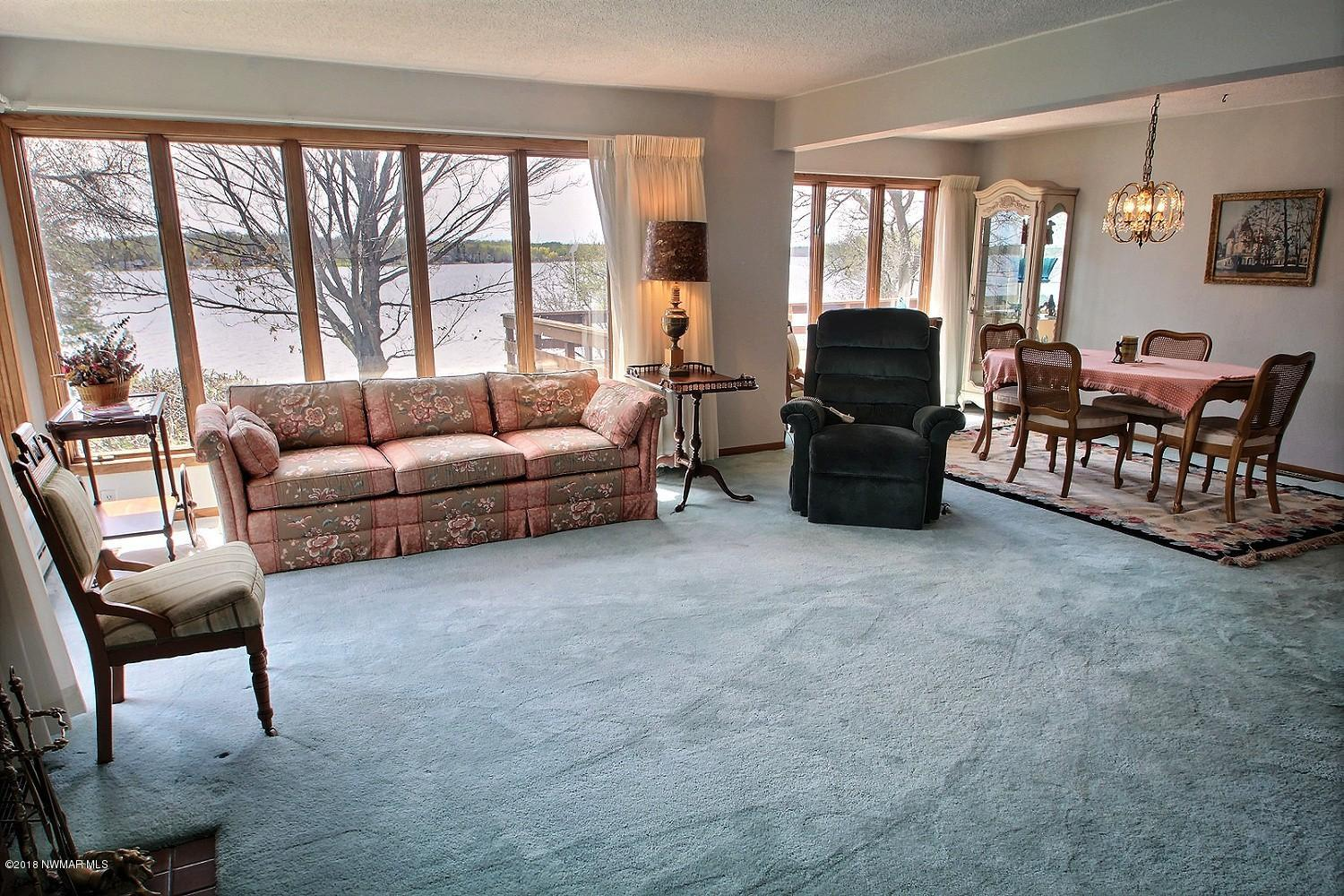 View of the wall of glass that the living room offers. The living room opens to the formal dining room with views of the shoreline.