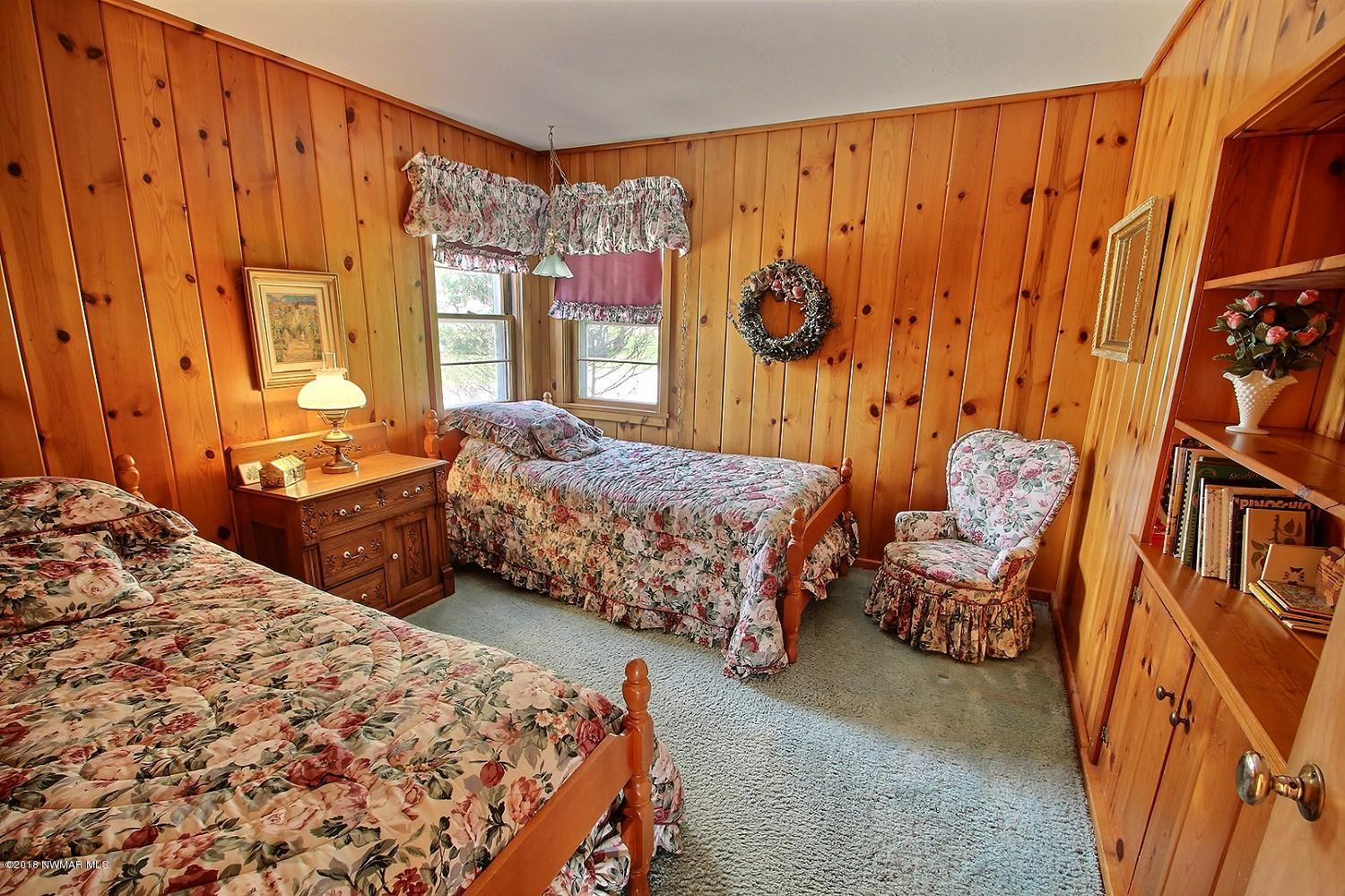 The second bedroom on the main floor offers knotty pine and built in book shelf.