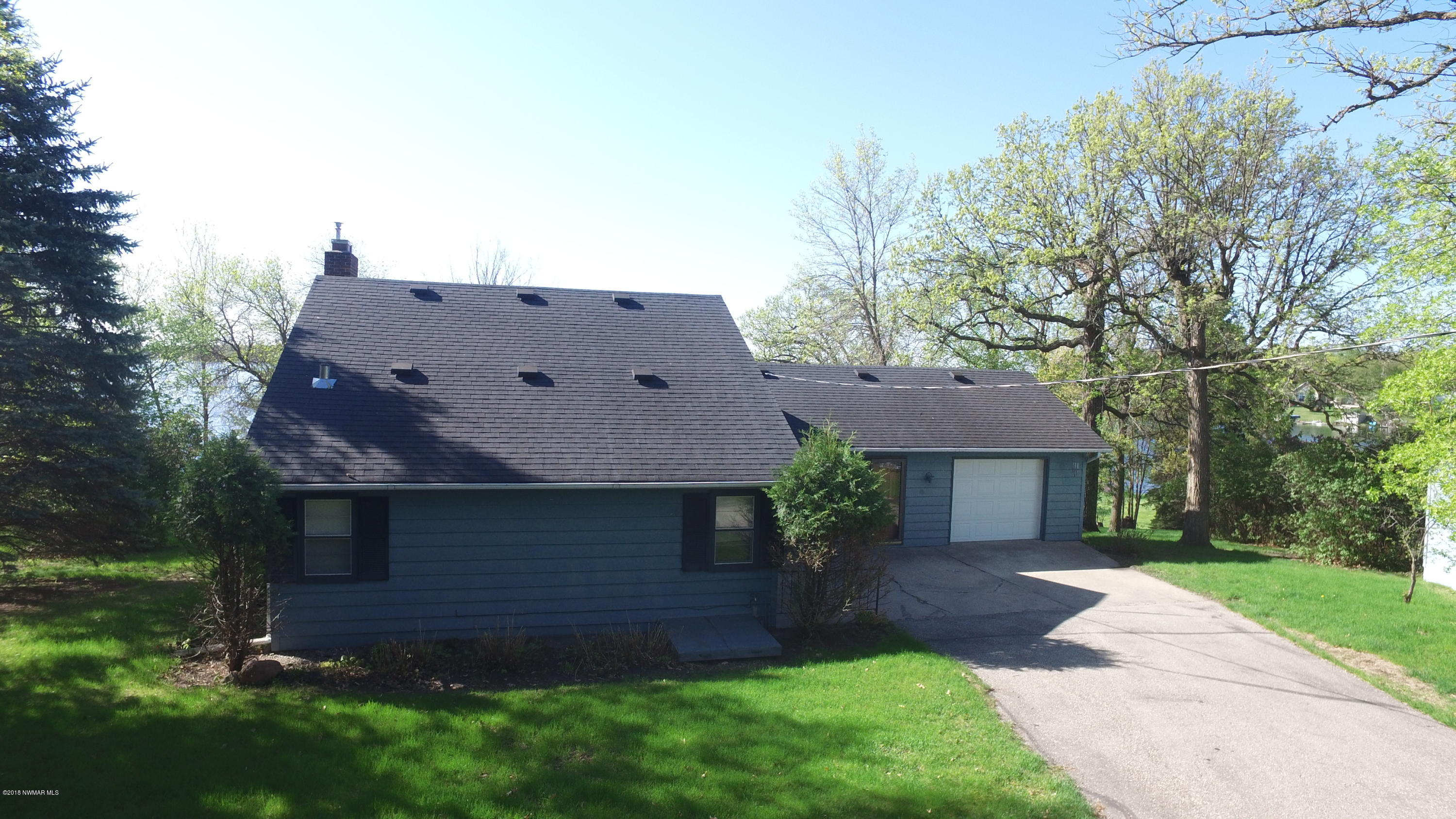 View of the home from the road. Offers an asphalt driveway and large concrete patio.