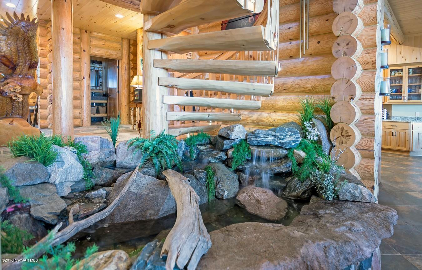 Above the water feature in the central part of the home is a custom built 9ft diameter circular log stairway.