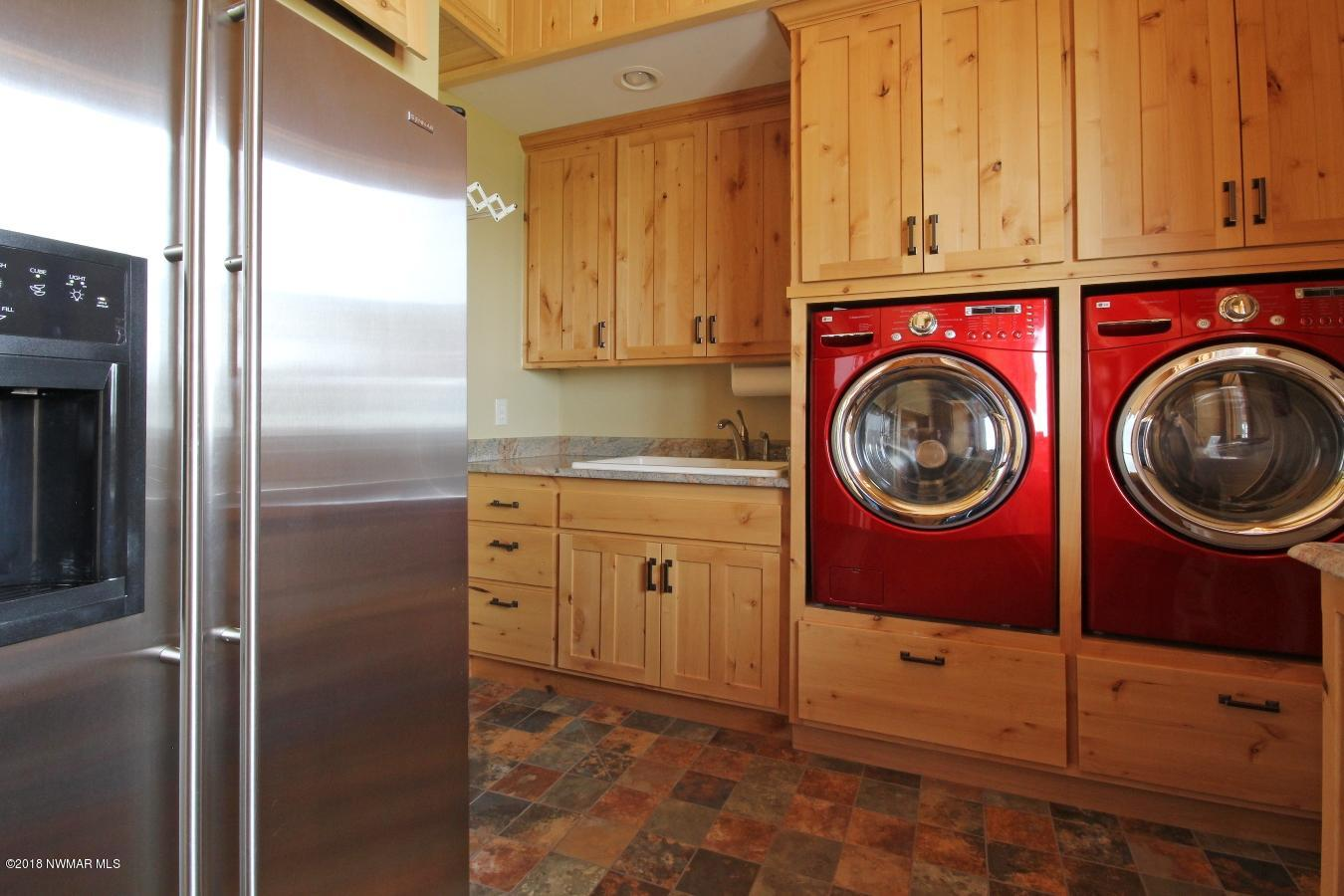 LG washer and dryer in the laundry room with granite folding area and overflow/beverage refrigerator and beach storage.