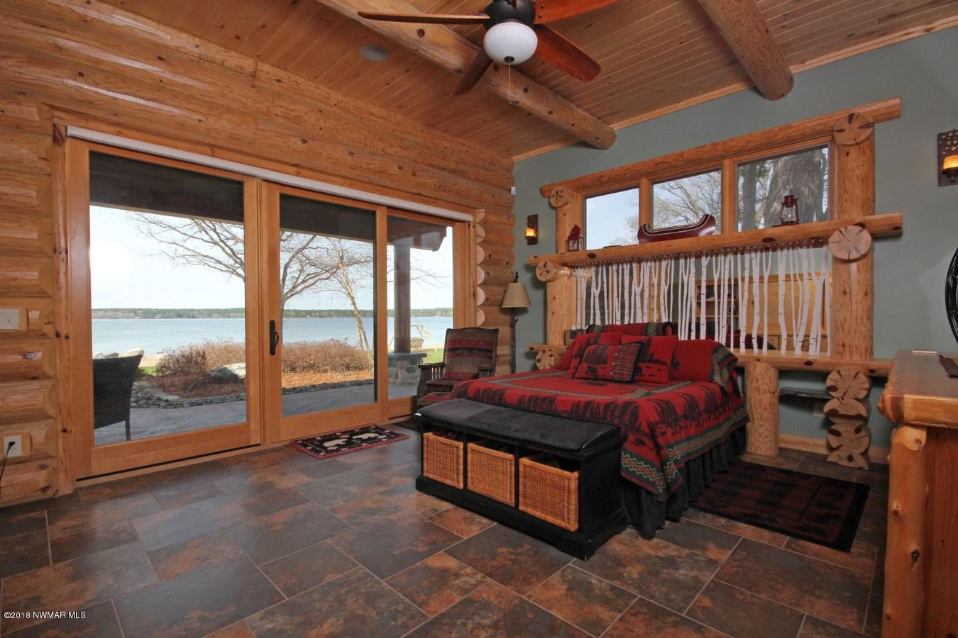 "Lakeside master bedroom on main floor with remote control shades and ""hideable"" television"