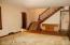 Pegged hardwood floor in living room with open stairway