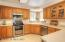 """The kitchen is spacious and has stainless steel appliances, a corner sink overlooks the pine trees and creates an """"Up-North"""" feeling."""