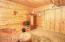 The fourth bedroom is in the lower level and has pine walls and ceiling.