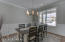 Dining Room with 9 ft ceilings, crown molding, custom wainscoting, hardwood floors and opens to foyer and kitchen