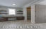 Large Mudroom with custom built-in lockers for 5, desk and open shelving, walk-in pantry closet and walk-in coat closet and half bath