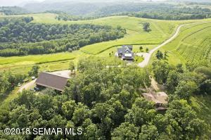 Aerial view of land, outbuilding, guest house and log home.
