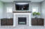 Gas fireplace with wooden mantel and built-in side cabinets as well as two transom windows for extra natural light