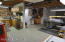 This is a large workshop with cabinets, counters, shelving and storage, 4 220v. outlets and access to the exterior.