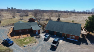 This aerial view shows the exterior of the home on the left, the garage on the right and the wood shed in the background.