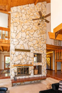 Gorgeous stone fireplace spanning two levels and open to family room, dining room, and master bedroom!