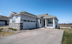 Newer twin home style with private drive. Nice stone accents, front porch, side load garage.