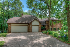 Front of home with paver stone driveway including turn around