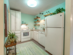 Warm and inviting kitchen with floating shelves and a huge pantry!