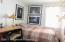 Guest bedroom with hardwood flooring