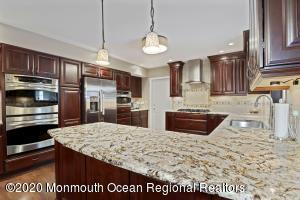 Stunning newer Kitchen with Cherry Wood Cabinets, Granite Countertops, tiled backsplash, wood flooring and full appliance package