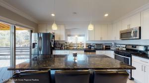 A great kitchen to live in! White cabinets, granite countertops, large island with seating space, sliding doors to the deck/backyard, and right off the dining room.