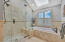 Shower with a built-in seat and seamless door, and Kohler soaking tub.