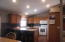 There is Ceramic tile Back-splash & a Vaulted ceiling with recessed lighting.