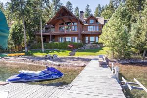 Lakefront living on Conrad Point Rd. Terraced lawn to pebble beach and dock.