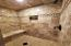 Master shower with custom tile & stone sitting bench and built in shelf design