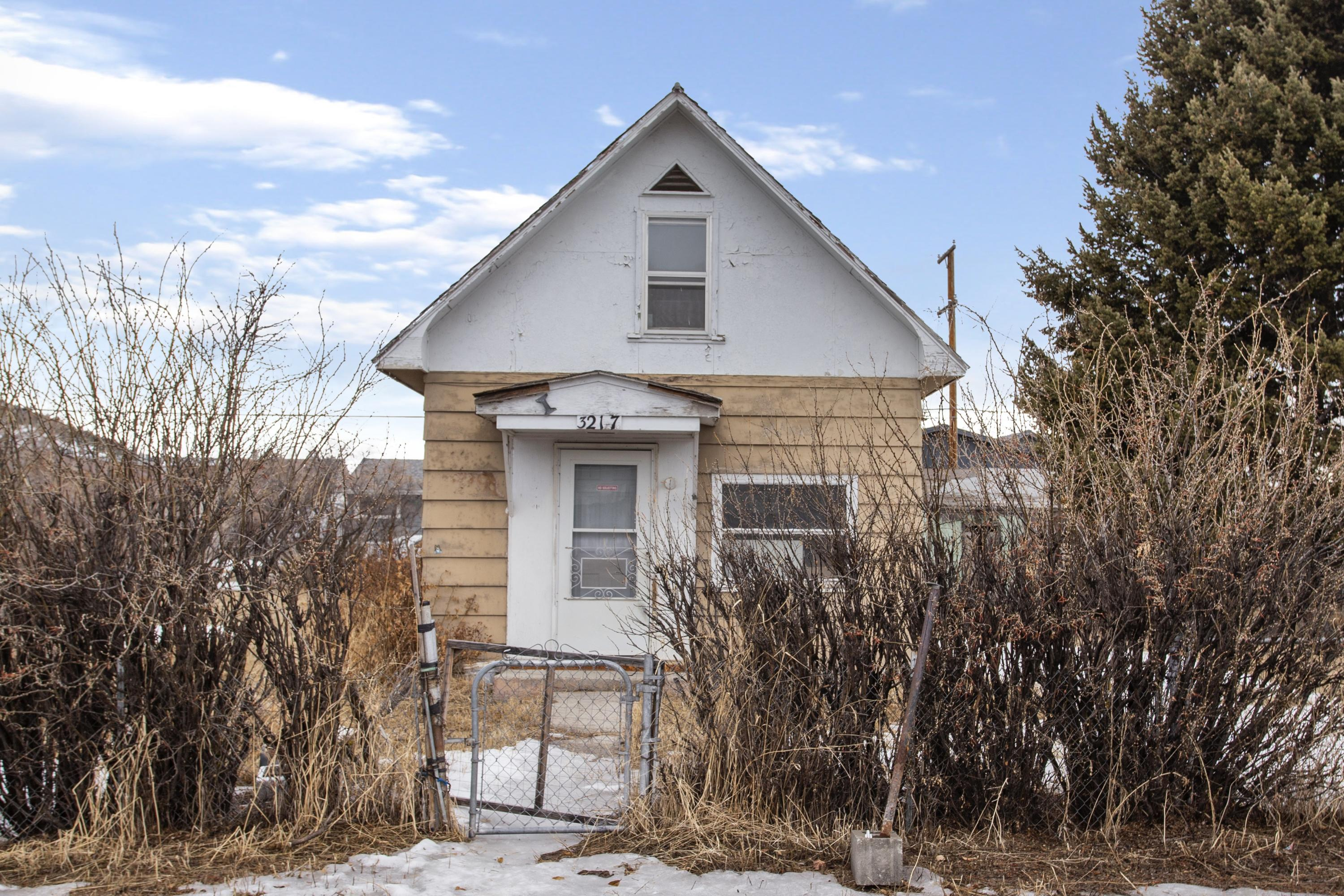 Talk about an opportunity! Much of the hard stuff has been done on this 2 bedroom, 1 bathroom home on the flats of Butte. You won't have to worry about electrical-- there is a new panel and wiring in place. The flooring throughout is low-maintenance, waterproof vinyl plank. Interior walls have been insulated and freshly painted, and you'll stay cozy with a new Rinnai gas wall heater. Even the bathroom got an updated bath/shower insert. And there is still plenty of original charm remaining with a curved staircase, archway, and built-ins. Ready to make the kitchen your own? The cabinets and trim convey with the sale. And perhaps the best part? The house is located in the middle of a huge 10,000+ square foot fenced lot with mature trees, lilacs, and poppies.  Selling ''AS-IS''.