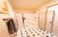 The master bath has a private shower and toilet area.