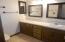Large oak vanity area w/plenty of mirrors.