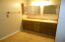Oak cabinetry in master bath w/good lighting and mirrors.