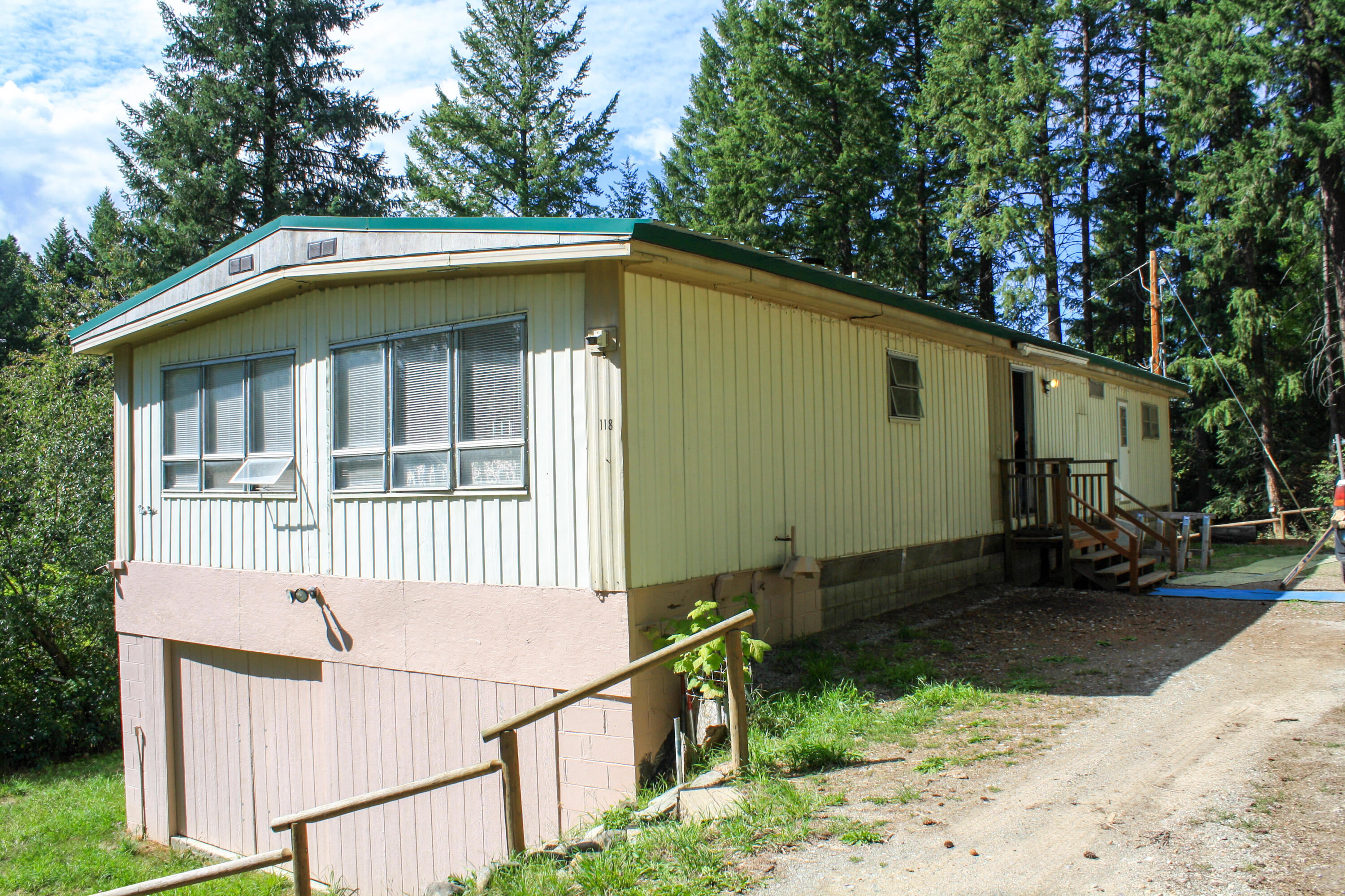 LOOK AT ME! This home has new carpeting and vinyl flooring throughout, new paint, new mini blinds in the living room/dining room, new stove, new vent hood, new toilet. Featuring 3 bedrooms/2 bathrooms, a separate dining room, with built-in cabinetry, adjacent to the living room and kitchen as well. This doublewide is de-titled and has a full basement on a permanent foundation. The home sits in the middle of trees and has a nice deck with views of the mountains through the trees. It's bordered by over 70 acres of the Stimson Lumber Company to the north.  Call/text Carolyn Daughton at 406-291-3782, or your real estate professional.