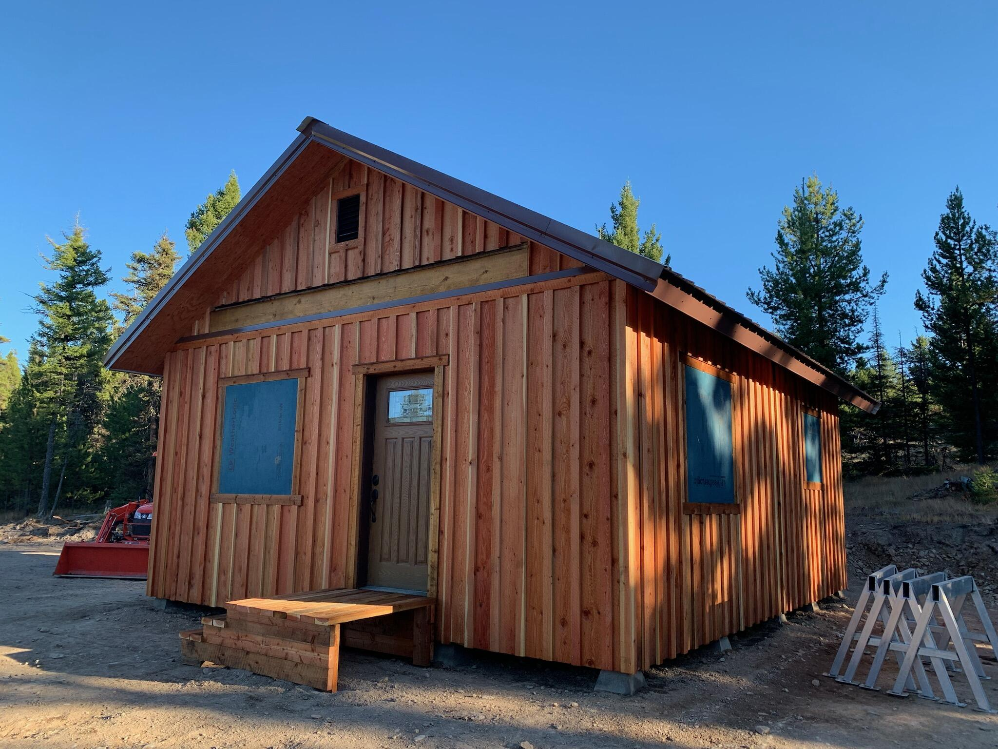 NEW 2021 off grid FRAME CABIN SHELL WITH INTERIOR FRAMING FOR KITCHEN/LIVING ROOM, BEDROOM, BATHROOM,  build out of full dimension lumber, new windows and doors, metal roof , newly treated board and batten  exterior.  Aluminum truck body with roll up locking door for atv storage, functional outhouse.Large spring in North east corner of the 20, spring planned for cabin use in the NW corner of the property,  Chimney creek runs through the West end of the property.  Another complete relic cabin on the East end of the property and two vintage bunkhouse / storage building in that area.  New cabin is in the area of the NORTH WEST  1/4 of the property.About 65% of the 20 acres is gentle slope/flat areas   timbered with new lodgepole, Alpine fir, mature doug fir in creek bottom.