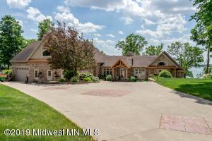 North Little McDonald is the setting for this custom built home designed for lake living and entertaining. Spectacular lake views from this spacious main floor living area that easily expands into beautifully landscaped lakeside patios. Kitchen includes professional stove, dual ovens, walk-in pantry, double dishwasher, custom hickory cabinets, maple flooring, and cedar throughout. Storage and counter space galore with all the upgrades. Main floor master suite offers seating area w/fireplace, Jacuzzi tub, spa shower and functional walk-in closet with built-ins. Power shades throughout home. Theater room w/72'TV 6 recliners, wet bar, beverage fridge and gas fireplace. Main floor guest room w/murphy bed. Hand scraped cedar hardwoods, tile and carpet throughout.