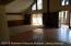 View of open living room with cathedral ceilings and wood burning stove