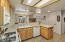 Kitchen has knotty oak cabinets and gas stove