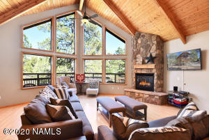 Grand livingroom with vaulted wood ceiling and fireplace.