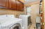 The laundry room has upgraded cabinetry and flooring to match the kitchen, full-sized washer and dryer, laundry sink, and plenty of storage for your clothes.