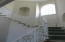 Dramatic curved Stairway with custom white iron railings