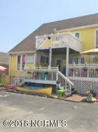 A colorful and inviting presentation from the street, with additional rear fenced back lot for storage, or expansion