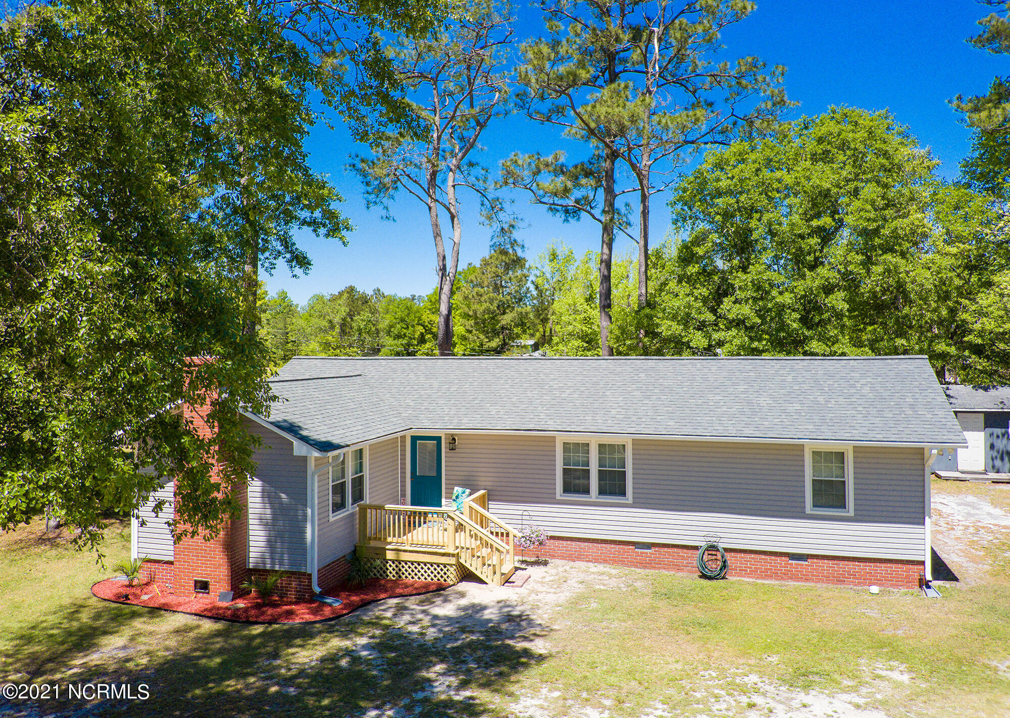 This beautifully updated, 2 bedroom, 2 full bathroom country-coastal home is nestled on just over an acre of private land surrounded by wildlife, gorgeous trees, and is only minutes away from a public boat ramp! Located within easy access to the ICW, residents enjoy cruising nearby coastal destinations in the area enjoying year-round boating conditions. The property is centrally located to Downtown Swansboro, Camp Lejeune, and Emerald Isle. No HOA or city taxes!  The spacious kitchen features a large center island that is perfect for entertaining guests! A large covered back porch and fire pit welcome you outside in addition to 3 out buildings including a multi-purpose shed up fitted with electricity to allow use for tinkering with tools/etc., a detached carport, and a small shed - perfect for additional storage.  The owners are currently working on rebuilding the front porch and will update photos upon completion. Owners have also recently installed a partial wood rear fence for additional privacy. New 40 yr Architectural Roof, new HVAC unit, all new vinyl windows, Victorian Grey Dutch Lap Vinyl Siding, 5'' seamless gutters. Master bath includes tiled walk-in shower, new vanity, ceramic tile flooring, and new fixtures just to name a few. New wood laminate flooring in Dining, Foyer, and Living Room. All new Luxury Vinyl in Master Bath, Guest Bath, Kitchen, and Bedrooms.  You will not want to miss out on the opportunity to call this special property home! This one won't last long folks!