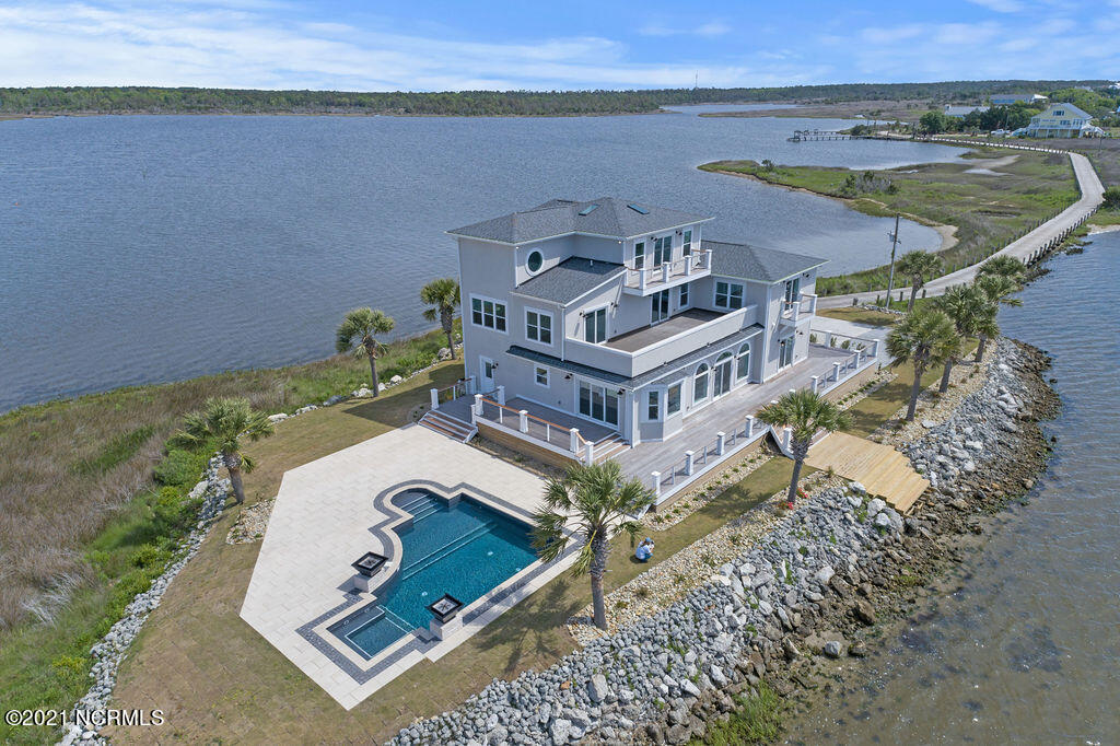Ever wanted to buy a home on your own private island? Here's your chance! This iconic and completely renovated 5 BR, 4 BA luxury gated waterfront home is situated on its own 4+ acre private island. Nestled between Topsail Island and Sneads Ferry, this 4534 square foot home named ''Waterway Island'' boasts stunning water views from every single window. 2 master suites with one on the main level, home office, open floor plan and ample entertaining space are just a few of the interior features. We're giving the buyer a rare opportunity to make the final selections of the home in order to finish it out to their own desire. List price includes allowances to complete all rooms. Enjoy the breathtaking water views outside on the wrap around deck & balconies. Best part? The impeccably designed saltwater pool has its own waterfall & fire features all while overlooking your private Intracoastal beach. The private dock is included in the allowance and will need to be approved by CAMA. Words cannot express the uniqueness of this home, it truly is one of a kind.