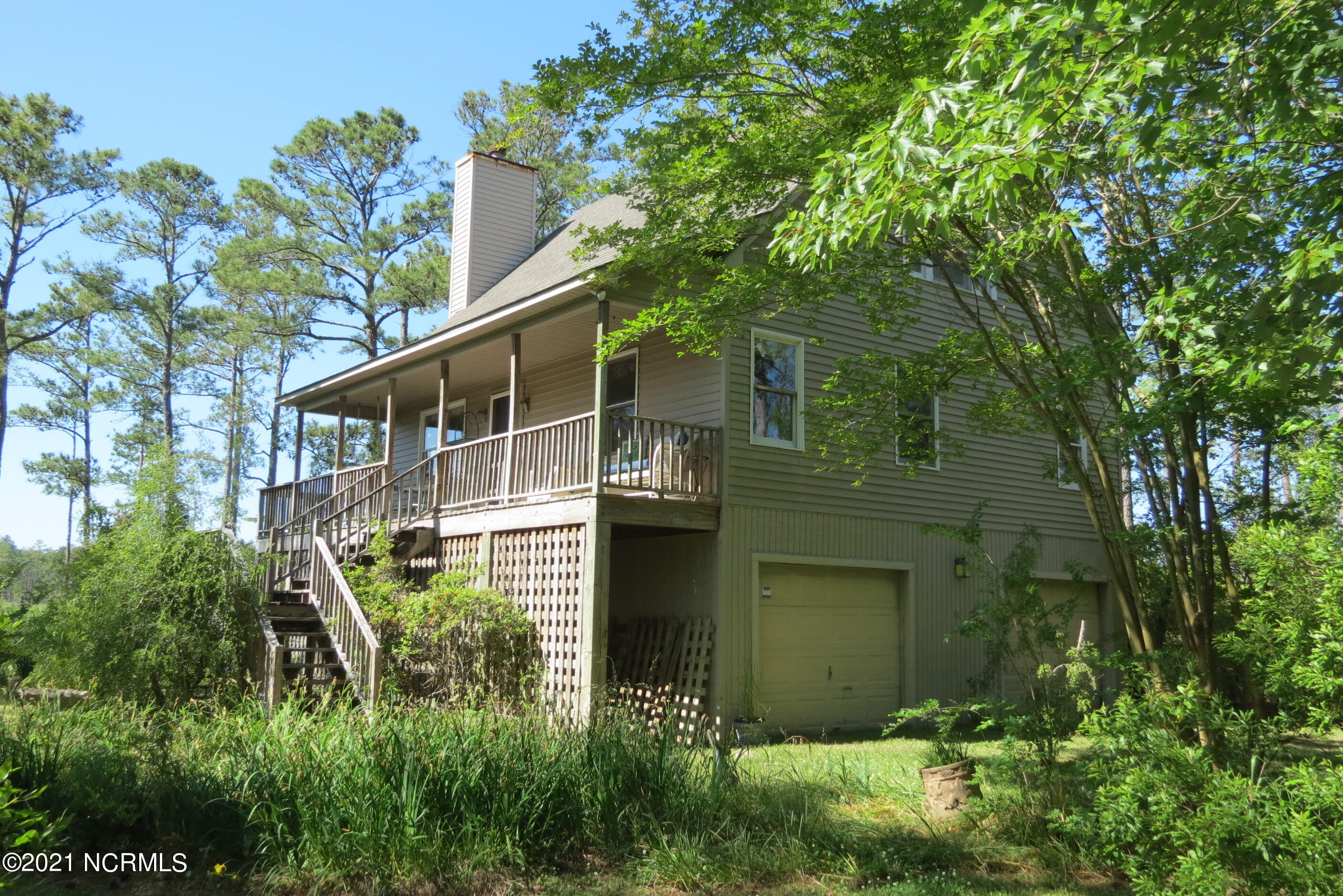 Your enticing waterfront getaway on deep and protected Spring Creek awaits, literally ''just around the corner'' from the ICW & the endless waters of the Pamlico Sound! Situated with utmost privacy on over 4.4 acres of deeply wooded waterfront acres, this two bedroom cottage is ready to deliver you a setting unlike any other! The moment you drive onto your long private lane, flanked by  the mature avenue of trees, you'll feel the cares of the world melt away. Your arrival at the residence, elevated gracefully above the fray, is welcoming & embraced by the naturalized surroundings... Allowing an unfolding of the delightful water views, which become more apparent and compelling with each step up the entry staircase. The amazing amount of creek frontage you possess (over 640' !) allows a sense of control over all surrounding vistas and a choice of locations from which to construct your pier. The home is low-maintenance and has served perfectly for many years as a family and artist's retreat. The abundant scenery and wildlife offers endless subjects for enjoyment, photography or painting. As you enter, the dramatic ceiling vaults to over 20' to the sunny loft area. The living room has a fireplace and communicates openly with the cheerful dining area and the efficient cottage kitchen - all with great views across the wraparound porch/deck to the waters beyond! A private master bedroom occupies a quiet corner and it has the laundry closet & bath (w/ whirlpool and shower) close by. The upstairs operates as a huge suite, with full bath, large bedroom and lofted family area, which has been used for extra guests. Plenty of storage in the house and under, too. The understory has two garage doors & potential workshop area, too. The screened porch is off the dining area and would be splendid for al-fresco meals. The deck is sunny and connects to a covered seating porch. Lots of expansion room and acreage here at your private waterfront ''Shangri-La'' ! Great fishing & boating!