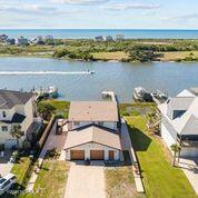 Unique opportunity to live on the ICWW with fantastic waterway views and ocean views from the top deck! Sip your morning coffee and watch the boats pass by or catch a pod of dolphins playing in the deep water. Recent upgrades include HVAC with digital thermostats, roof, paint, and flooring upstairs and down. The kitchen has been adorned with new cabinetry with LED 16 color lighting inside the glass doors, with soft close drawers and absolutely gorgeous Orinoco granite countertops. Stainless Samsung appliance package, and stainless farmhouse sink. High gloss floors upstairs and new LVP low maintenance floors downstairs. Downstairs is plumbed and wired for a kitchen/bar if you wanted to add that for downstairs guests. This is truly a well built home, and is raised up off grade on solid concrete. Very few homes available on the ICWW for sale so this is a great opportunity!
