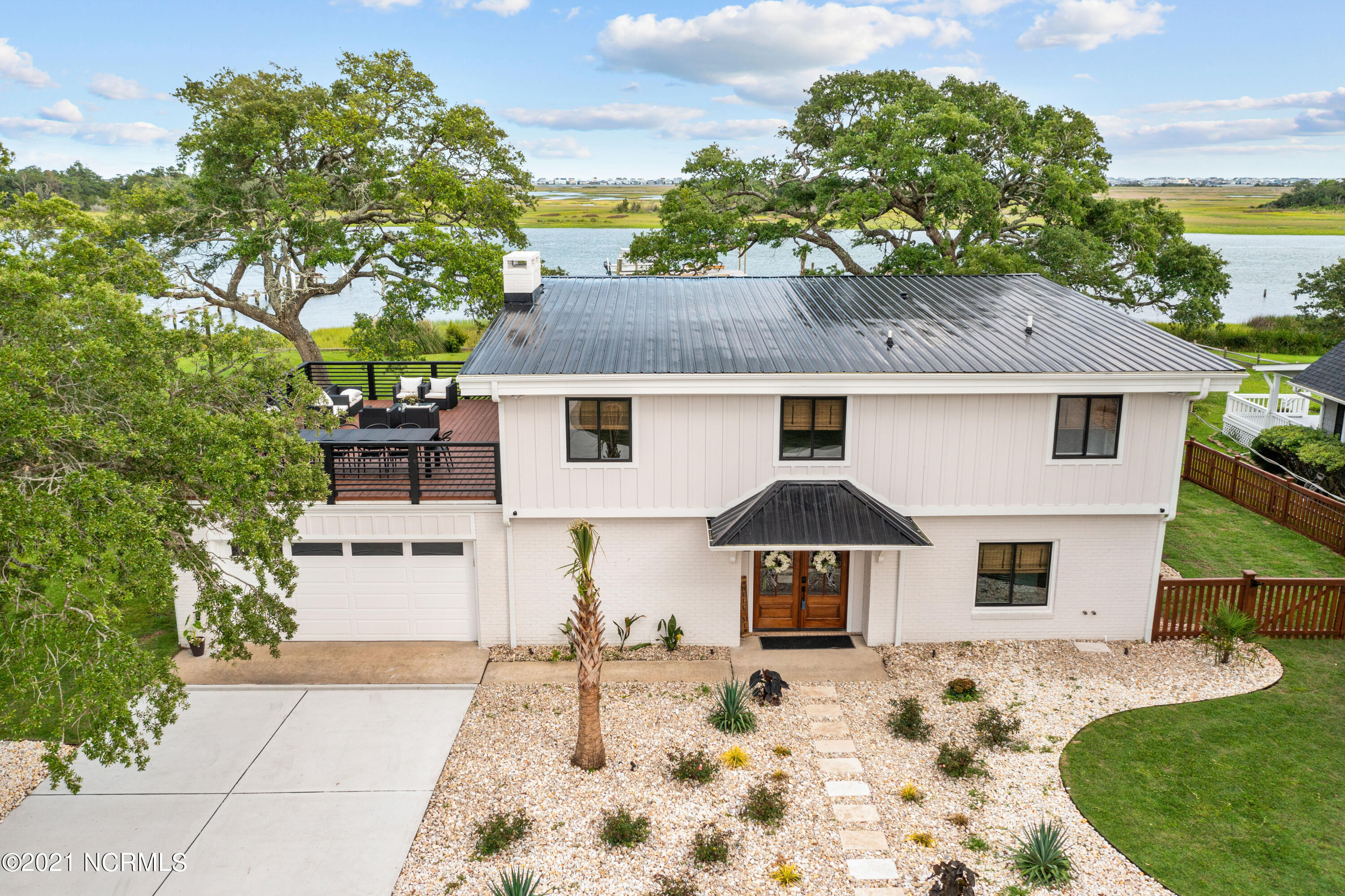 Exquisite waterfront home with private boat ramp, dock, 2 boat lifts, 3 wet slips, & stunning views of the Intracoastal Waterway. Located on a prime .64 acre lot, this 2,867 sqft, 4 bedroom, 3 full bathroom home is every boater's dream. Enjoy your coffee on the gazebo soaking up the coastal sunrise & end your day with a sunset cruise around the nearby inlets. Main floor features a desirable open floor layout, luxury vinyl plank flooring, shiplap details, painted wooden beams, & contemporary features. Stunning views of the ICW are visible from every angle. Kitchen features quartz countertops, GE Cafe Series appliances with a 6-burner gas range, a quartz/granite sink, & large center island. Step out onto the screened porch overlooking the waterway for a cozy afternoon or enjoy a cookout with friends & family on the spacious wooden deck. Incredible master suite boasts panoramic views of the ICW, a private screened porch, tile bathroom floors, dual vanities, freestanding soaking tub, & tiled shower with dual shower heads. A second bedroom & full bathroom complete the main floor. Downstairs is a large flex room complete with a wet bar, beverage fridge, and brick fireplace. Two bedrooms, a spacious full bathroom, & a sizable laundry room finish the interior. Sliding glass doors open up to a large patio overlooking live oak trees and the breathtaking water view. Private dock with power and water access leads to 5 boat slips--two 30' wet slips, two 10,000 lb remote-controlled boat lifts, and space for a 45' vessel with a private boat ramp deep enough to launch a 25' vessel. 15' deep at end of the gazebo. Property also includes a 201 sqft heated/cooled separate bunk house and a storage shed for all tools. Other features include a metal roof, fenced-in side yard, oversized two-car garage, new water softener, wide circular driveway, tankless water heater, & outdoor shower. Don't miss out on this incredible opportunity to own your coastal paradise--call today to make it yours!