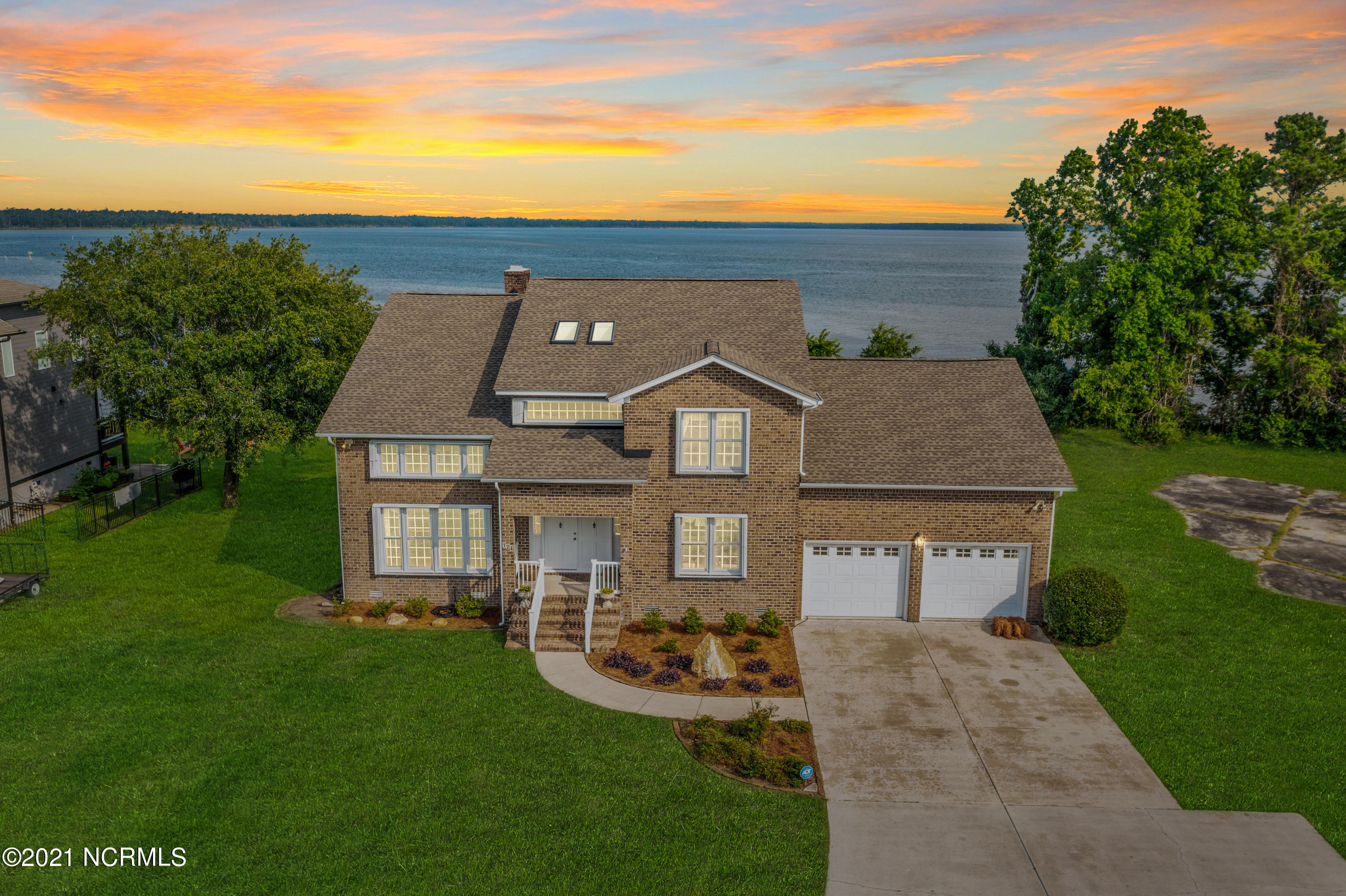 From the moment you arrive at this stunning waterfront property, that does not require flood insurance, you know this is a special place to call home. Immaculate gardens and manicured lawns welcome you while a porch invites you to step inside and discover the heart and soul of this elegant beauty.  Built in 1989, this is the first time this residence has been offered for sale and it has never been rented so you will be only the second owner to enjoy this luxurious lifestyle. Inside, a beautiful blend of original features and modern comforts combine to ensure a home you'll be proud to call your own.  A grand double-height entrance foyer sets the tone, with a curved staircase leading to the upper level where you will discover the decadent owner's suite. Here, parquetry flooring flows underfoot paired with a fireplace, a luxe ensuite and French doors that open out to the upper-level balcony.  The living spaces on the lower level include a formal living room and an elegant dining room, plus a family room with a fireplace and a breakfast nook that enjoys sweeping views over the lawn and out to the water. The well-equipped kitchen will delight anyone who loves to cook and there is also a rear patio where you can relish year-round entertaining.  Outside, the alfresco living spaces have been crafted to make the most of the sensational water views. You can start your day with a coffee in hand on the lower deck as you overlook the land or take the spiral staircase to the elevated deck and really take in that panoramic vista.  For the boating enthusiast, a dock is in need of rebuilding, offering the perfect chance for you to create the perfect dock to suit your needs. If you have dreams of further expansion or perhaps a boathouse or detached guest suite, then the neighboring, vacant key-shaped lot is the perfect space to bring your plans to life. Available for sale, this is a great way to instantly expand your land and enjoy an expansive private water front